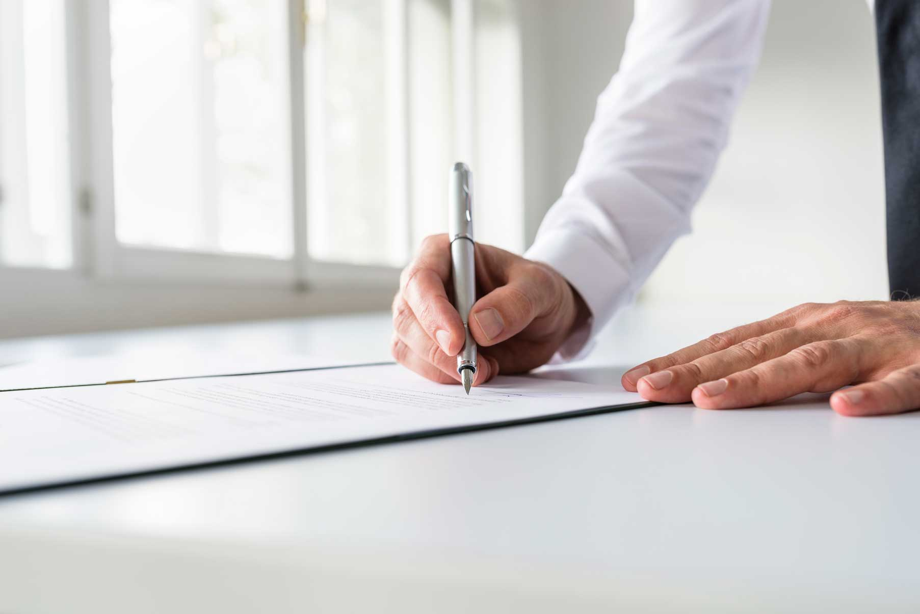businessman-in-white-shirt-signing-contract-NZ5FRLH